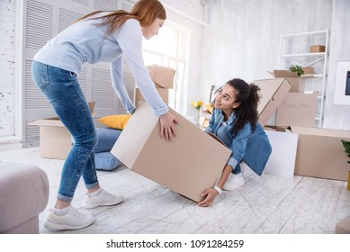Mutual assistance. Kind young girl helping her roommate to lift up a heavy box while packing their belongings before moving out of the shared flat