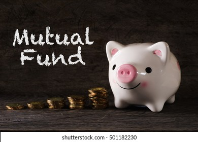 """""""Mutual fund"""" words with Piggy bank and stack of golden money increased with wooden background - saving, finance and business concept"""