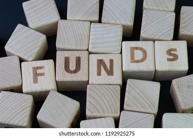 Mutual funds, investment asset selection by performance concept, cube wooden block with alphabet combine the word abbreviation FUNDs on black chalkboard background.