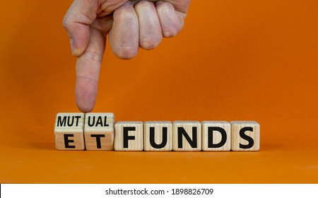 Mutual funds vs ETF symbol. Businessman turns a cube and changes words 'ETF, Exchange-Traded Fund' to 'Mutual funds. Beautiful orange background, copy space. Business and ETF vs mutual funds concept.