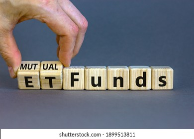 Mutual funds vs ETF symbol. Businessman turns a cube and changes words 'ETF, Exchange-Traded Fund' to 'Mutual funds. Beautiful grey background, copy space. Business and ETF vs mutual funds concept.