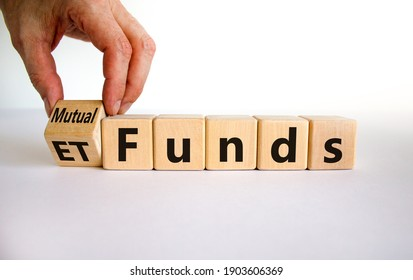 Mutual funds vs ETF symbol. Businessman turns a cube and changes words 'ETF' to 'mutual funds'. Beautiful white background, copy space. Business and ETF and mutual funds concept.