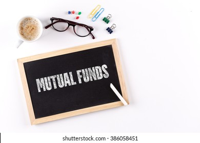 MUTUAL FUNDS word on Chalkboard with Coffee Cup, view from above
