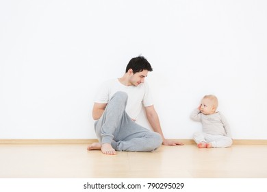 Mutual understanding between children and their parents. Young father tries to understand his little son. Lifestyle family portrait on white wall background at home. Copy space