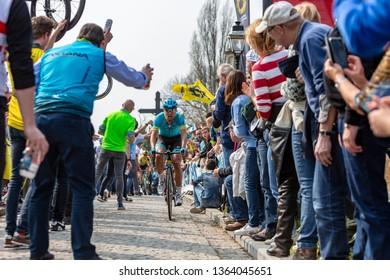 Muur van Geraardsbergen, Belgium - April 7, 2019 : The cyclist Magnus Cort Nielsen r through a crowd of excited psectators on the top of the famous Muur van Geraardsbergen during Tour of Flanders 2019