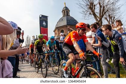 Muur van Geraardsbergen, Belgium - April 7, 2019 : The peloton is passing through a crowd of excited psectators on the top of the famous Muur van Geraardsbergen during Tour of Flanders 2019.