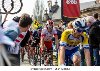 Muur van Geraardsbergen, Belgium - April 7, 2019 : The cyclist Cyril Lemoine of Team Cofidis passes through a crowd of spectators on the top of Muur van Geraardsbergen during Tour of Flanders 2019.