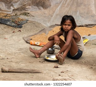 Muzaffarpur, India - February 21, 2019: A young poor girl sitting on the ground and eating her food.