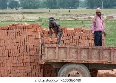 Muzaffarpur, India - February 28, 2019: Bricks stacked together at the location of brick kiln. Labourers are in the process of loading the bricks on the tractor for transportation