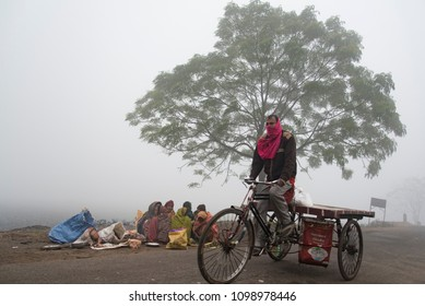 Muzaffarpur, India - Januray 15, 2018: A group of poor homeless people sittting near a tree in an outdoor location in the cold while a tricycle rider rides past.