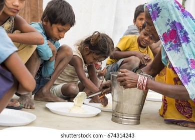 Muzaffarpur, India - May 10, 2017: A lady feeding food to poor children in a remote village in India. India ranked 97th out of 118 countries on the IFPRI's Global Hunger Index (GHI) in 2016.