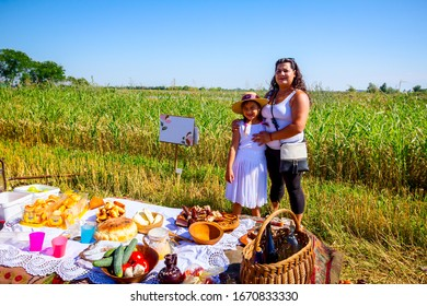 Muzlja, Vojvodina, Serbia, - July 06, 2019; Gypsy mother and daughter are ready for breakfast on picnic at XXXVI traditional wheat harvest.