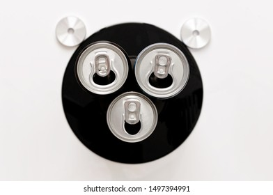 The muzzle of a bear or a monkey. Abstract art composition of three drink cans, vinyl record and turntable record adapters.