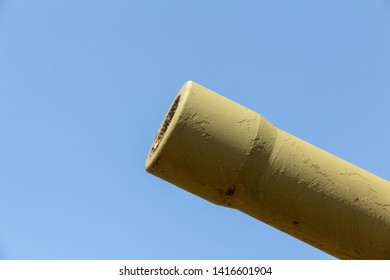 Muzzle brake heavy cannon against a blue sky. Howitzer gun. Artillery barrel. A fragment of an artillery gun barrel. concept for war or army weapons