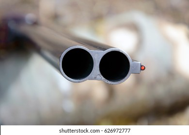 Muzzle of double-barreled shotguns. Shotgun pointed at me - macro shooting. Hunting rifle takes aim at the victim. Eyes on the target.
