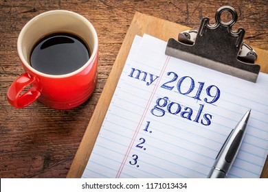 my 2019 goals list on clipboard and coffee against grunge wood desk