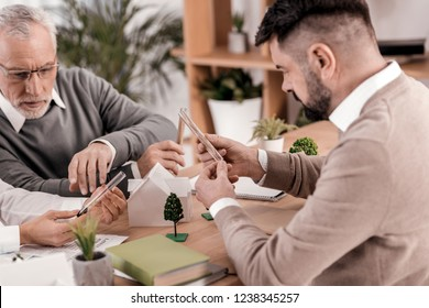 My analysis. Determined bearded ecologist sitting the table and looking at the beaker