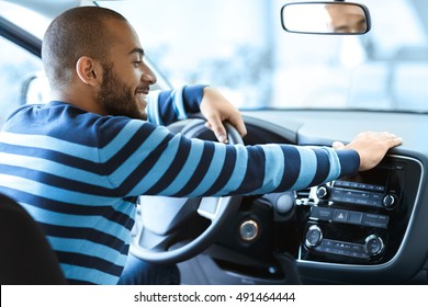 My baby. Shot of a happy man sitting in his car touching the dashboard gently smiling cheerfully
