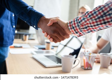 My congratulations! Two cheerful businessmen shaking hands while being in office together with their colleagues