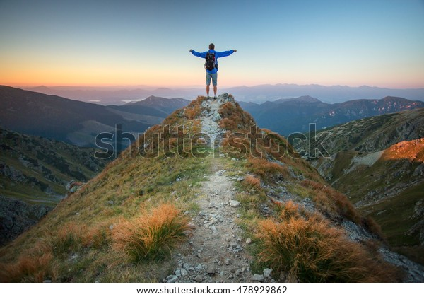 My country, my home. Man on top of mountain massif. Idyllic evening - a man on the ridge of the Low Tatras at sunset. Self Portrait in a mountain area.