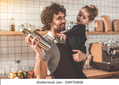 My daddy job. Cheerful man is looking after his little daughter while shaking beverage in cafeteria. Girl is pointing finger at shaker with interest