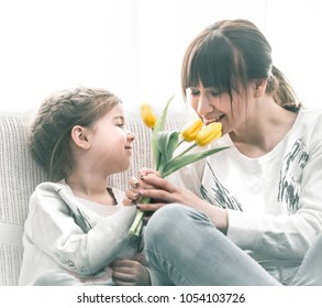 My daughter gives mother yellow tulips, the concept of Mother's Day, family comfort and family relations