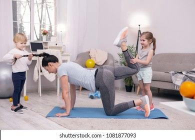 My day off. Concentrated young mother stretching herself and her kids helping her