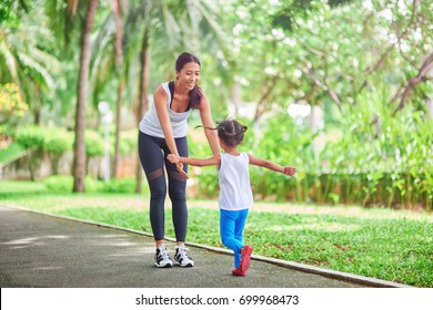 My dear. Cute little girl running in front of her loving sporty mother while standing in the park and spending time together