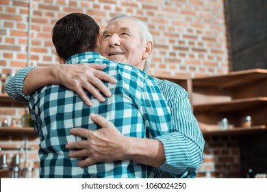 My family. Nice delighted aged man hugging his son and smiling while expressing his love to him