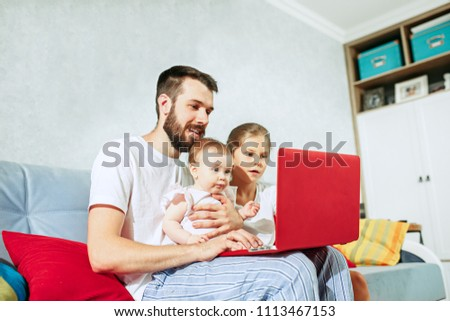 My favorite. Proud father and his daughters at home with laptop. Child 8 months of age. Happy father's day concept
