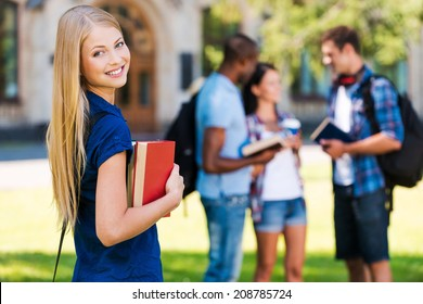 My future is in my hands. Beautiful young woman holding books and smiling while standing near university building and with her friends chatting in the background
