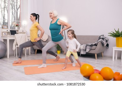 My girls. Delighted grey-haired woman smiling and exercising with her daughter and granddaughter