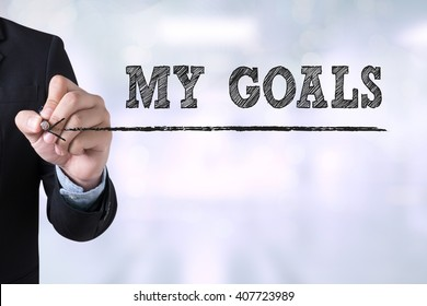 MY GOALS Businessman drawing Landing Page on blurred abstract background