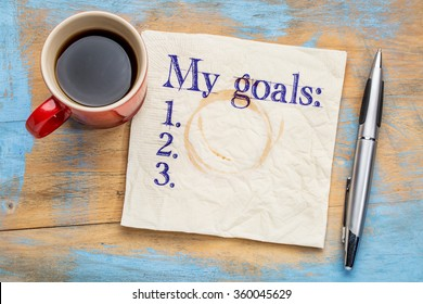 my goals list on a stained napkin against grunge wood table with  a cup of coffee