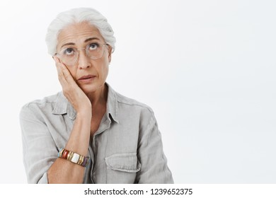 My god such stupid generation. Portrait of bothered and irritated displeased senior woman in glasses rolling eyes up from annoyance holding palm on chin reacting to dumb and nonsense talk