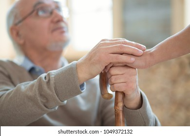 My gratitude. Selective focus of wooden cane and senior male hands holding it and putting other hand on female hand