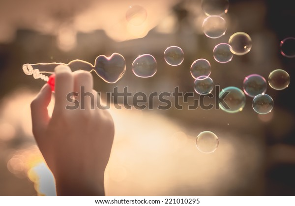 My Heart Bubbles at the sky, sunset,Love in the summer sun with bubble blower,romantic inflating colorful soap bubbles in park