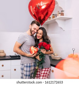 My heart is yours. A lovely couple is celebrating Valentine's Day at home in a cozy atmosphere, wearing pajamas, hugging and giving each other flowers and presents.