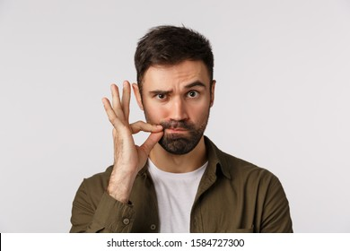 My lips are sealed with promise. Serious and funny bearded adult man keep mouth shut, making zip gesture and raise one eyebrow as hinting person stay silent, keep secret safe, white background