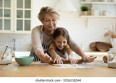 My little helper. Active aged grandma involve small grandkid girl in rolling yeast cookie dough with wooden pin. Caring elderly granny sharing skills in baking homemade pastries with little grandchild