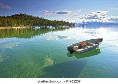 My lonely little fishing  boat setting on the Calm clear water in lake Tahoe, with Trees and Mountains in the background