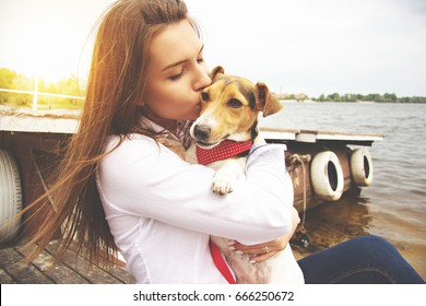 My lovely pet. Close-up portrait of happy, young and beautiful woman in casual clothes is kissing little cute dog while keeping dog in hands and sitting on pier.