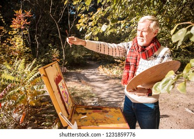 My masterpiece. Nice talented artist standing near the easel while creating a new painting