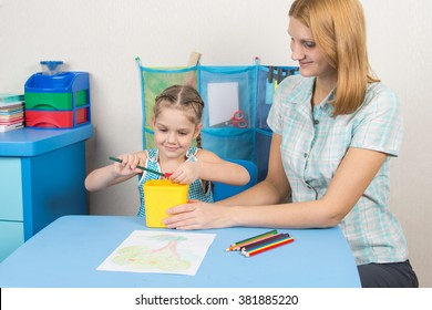 My mother helps the child to sharpen pencils