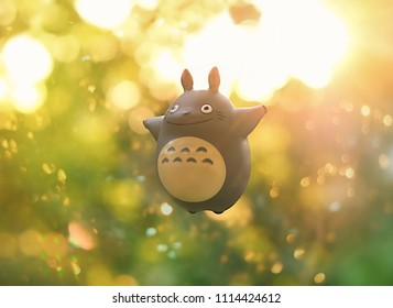 My Neighbor Totoro. toy Totoro, character from anime of Hayao Miyazaki. toy Totoro on blurred nature summer background. Russia, Moscow, June 2018