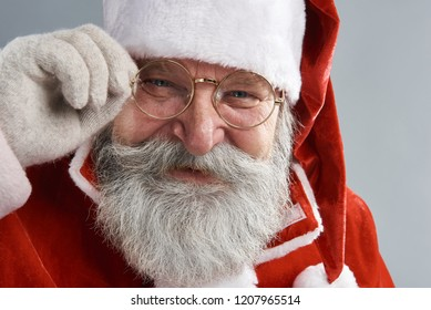 My new glasses. Close up portrait of joyful old man in Santa hat looking at camera with happy smile