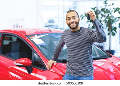 My new wheels. Attractive young African man smiling happily holding car keys to his newly bought car posing at the dealership copyspace driver owner purchase consumerism happiness buying a car concept
