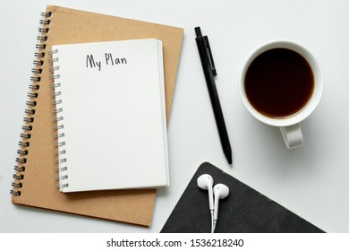 My plan on blank notebook with coffee, pen and earphone on white background, top view.