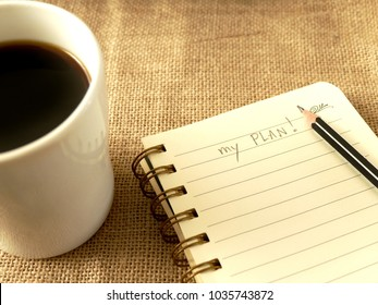 my plan word, message on the notebook or diary with the black coffee on the table