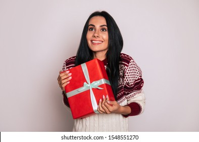 My precious. Cute young adult girl is holding a gift in a red box near her chest, smiling broadly and looking upwards with joy.